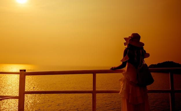 日没時に一人でシルエットの女性。悲しくて寂しい。夏の海とビーチ。旅行と休暇。