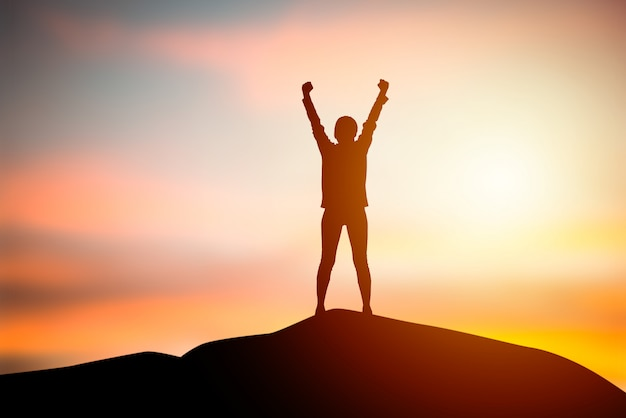 立っているシルエットの女性は、ぼやけて夕日を背景に両手を上げます。自由の概念、人生の成功。ビジネスと組織の目標。旅行と冒険のコンセプト