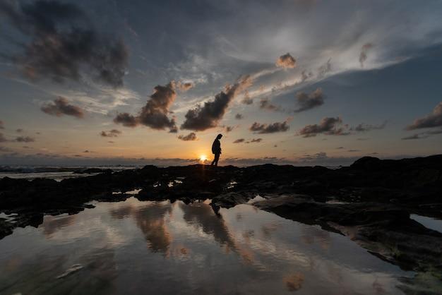 日没時間と反射池の美しい曇り空のシルエットの女性/背景テクスチャ/自然空