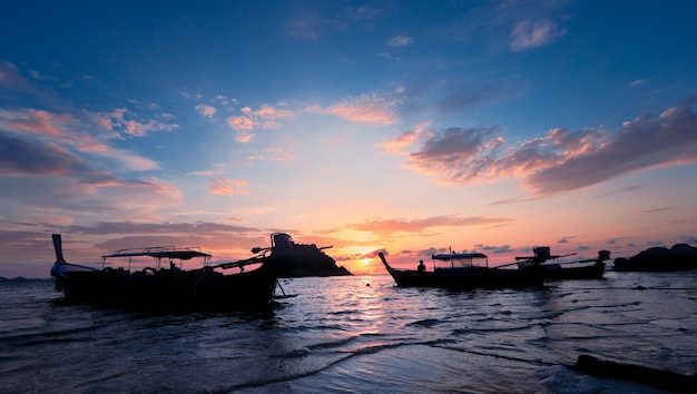 Silhouette of wooden boat in sea with sunset and blue sky at lepe island in thailand