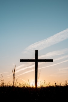 Silhouette of wooden cross in a grassy field with a blue sky in the background in a vertical shot