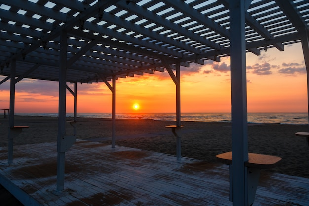 Silhouette of a wooden gazebo at sunset on a deserted beach