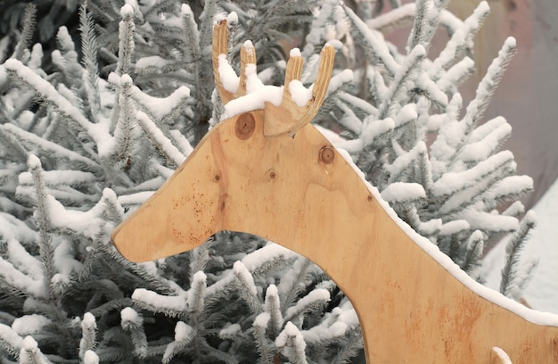Silhouette of wooden reindeer with snow