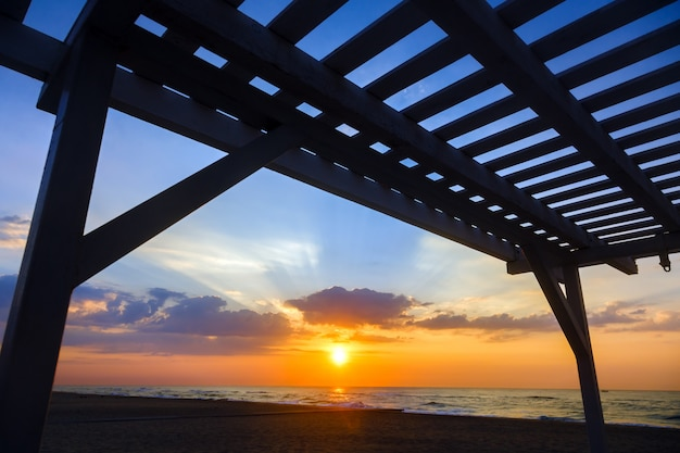 Silhouette of a wooden structure at sunset on a deserted beach