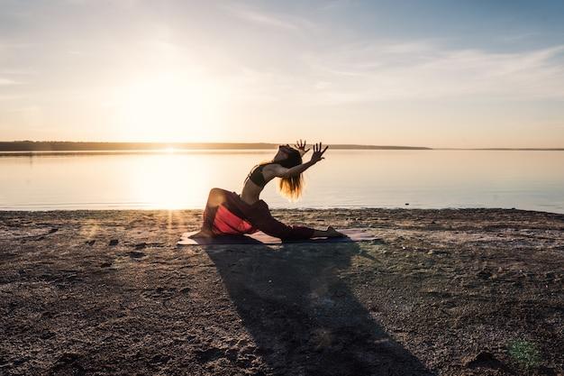 日没時のビーチでシルエットヨガの女性。朝の自然トレーニング