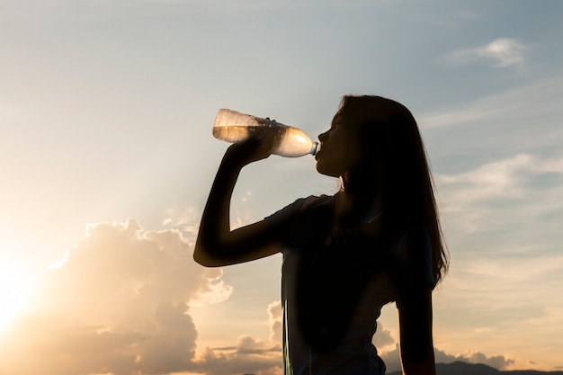 Silhouette young asian woman drinking water after jogging