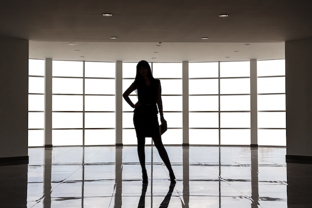 Silhouette of young attractive woman dressed in business suit with a short skirt is standing against the big empty window in a white office, holding a note book.