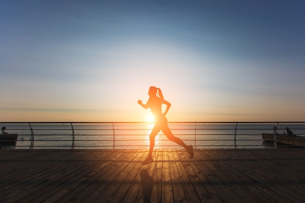 The silhouette of a young beautiful athletic girl with long blond hair in black clothes running at sunrise over the sea