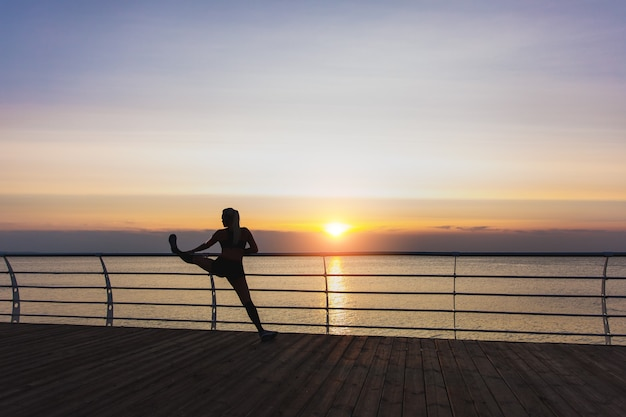 The silhouette of young beautiful athletic girl with long blond hair in headphones listening to music and doing stretching at sunrise over the sea, back view