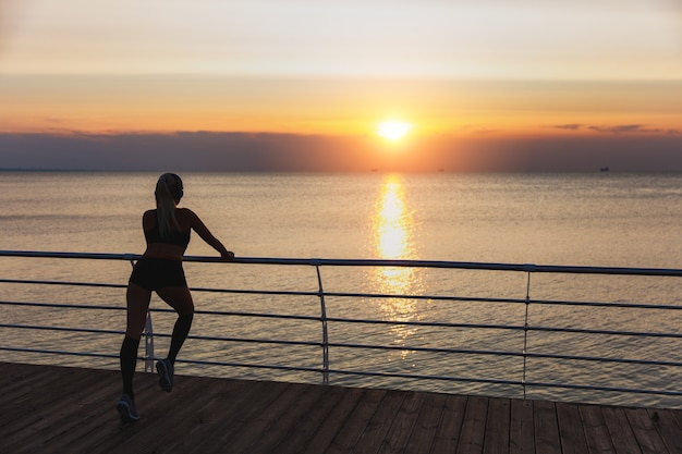 The silhouette of young beautiful athletic girl with long blond hair in headphones listening to music and training at sunrise over the sea, back view