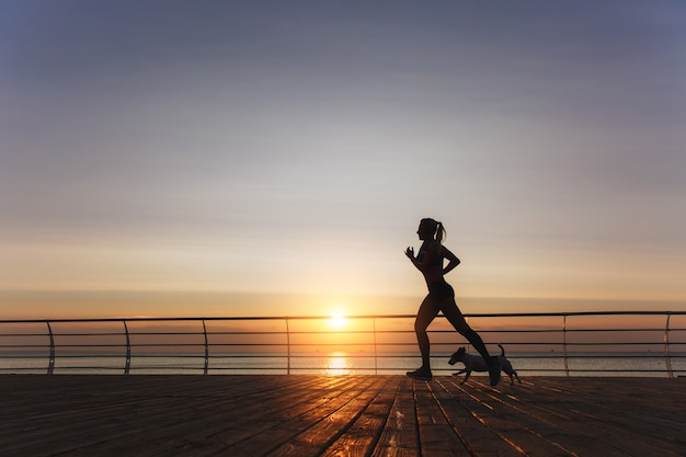 The silhouette of a young beautiful athletic girl with long blond hair in headphones that runs at dawn over the sea with her dog