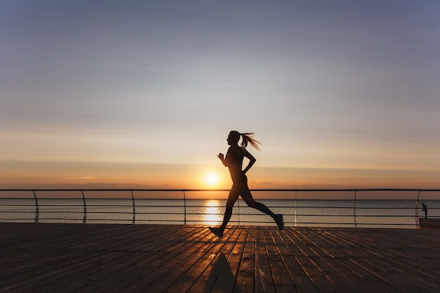The silhouette of a young beautiful athletic girl with long blond hair in headphones, who listens to music and runs at dawn over the sea