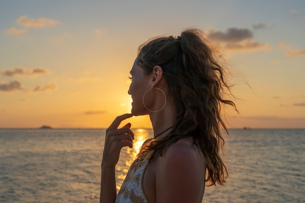 Silhouette of a young beauty girl at tropical beach near sea water at paradise island at sunset, close up. summer concept. holiday travel.