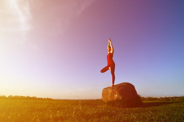 Silhouette of young blonde girl in sport suit practice yoga on a picturesque green hill in the evening at sunset.