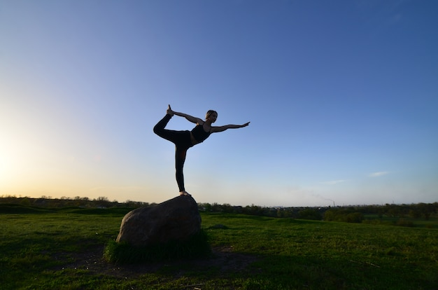 Silhouette of young blonde girl in sport suit practice yoga