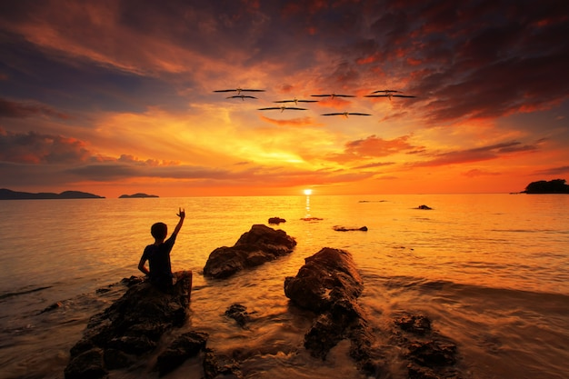 Silhouette of young boy show the love hand and standing on rock in the sea with sunset sky