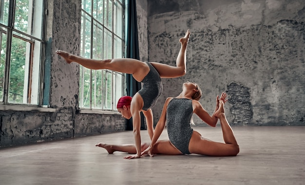 Silhouette of young cool attractive yogi woman practicing yoga concept, standing in adho mukha vrksasana exercise, downward facing tree pose and another girl sits in twine.