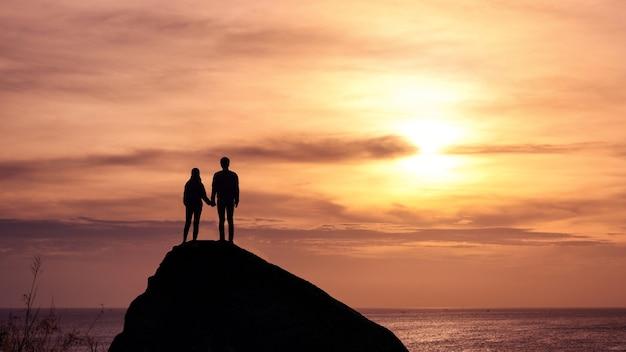 シルエットの若いカップルが熱帯の海の大きな岩に沈む夕日を見ている