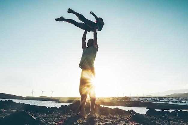 ビーチで屋外acroyogaをやっているシルエットの若いカップル-女と男の夕暮れ時の日没時のトレーニング-体にソフトフォーカス-健康的なライフスタイルのコンセプト