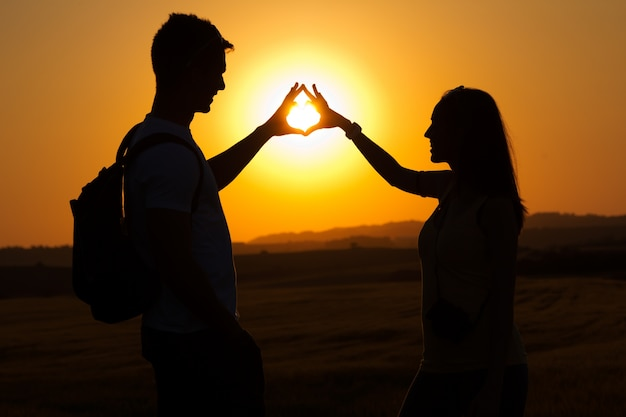Silhouette of young couple in field.