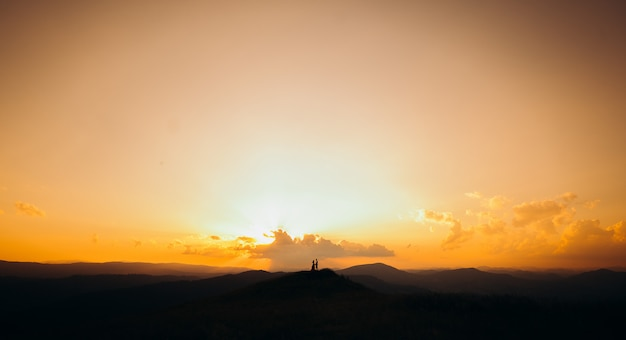 Silhouette of young couple in love enjoying a sunset over the mountains. girl in red dress.