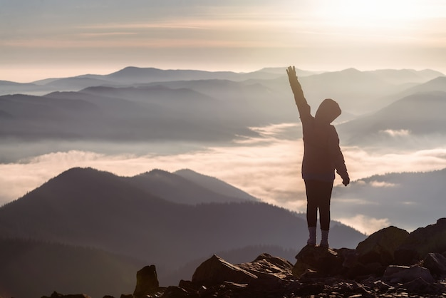 Silhouette of a young girl on a mountain peak with a raised hand above low clouds at dawn. success and victory concept.