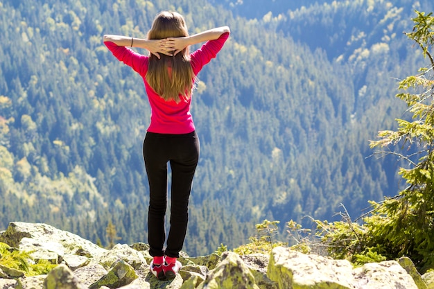 Silhouette of a young happy beautiful slim girl in red sweater standing on big rocks in mountains lifting hands