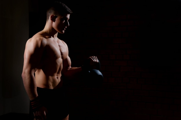 Silhouette of a young man doing weight exercises with a dumbbell