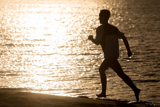 Silhouette of young man jogging at seashore