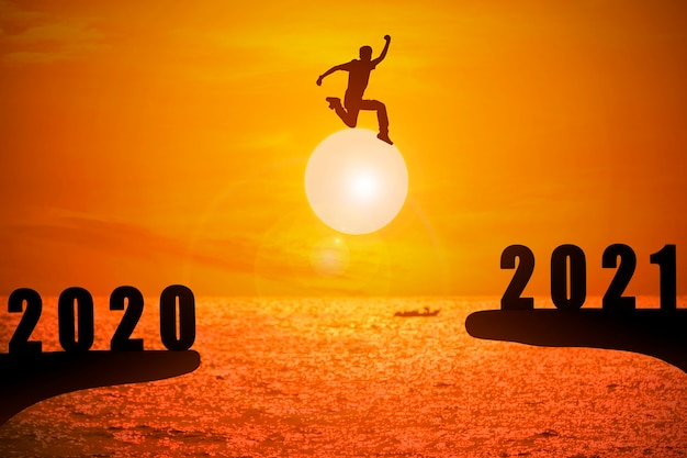 Silhouette of young man jumping between 2020 and 2021 years with beautiful sunset at the sea.