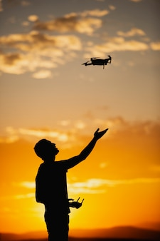 Silhouette of a young man operating a drone in a rural setting on sunset