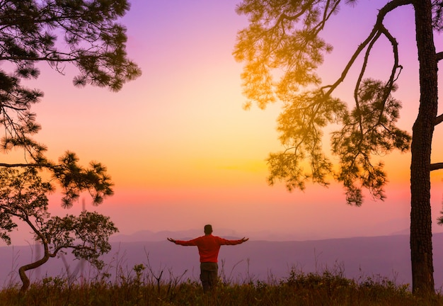 Silhouette of young man on sunset or sunrise in pine forest. confident teenage boy thinking.