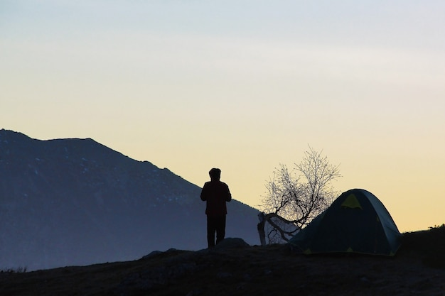Silhouette of a young man, a tent and a tree against the mountains