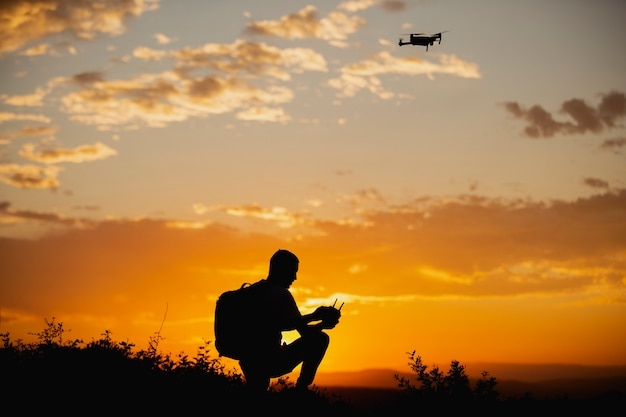 Silhouette of a young man with a backpack operating a drone in a rural setting on sunset