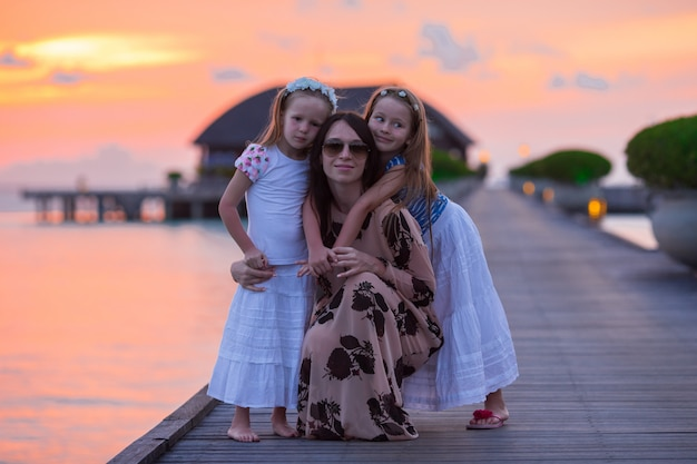 Silhouette of young mother and two her little girls at sunset