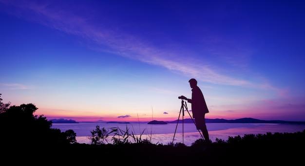 실루엣 젊은 사진 남자는 일출이나 일몰 아름다운 풍경에서 사진을 찍을