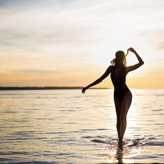 Silhouette of young sexy woman in bikini walking on the beach at sunset