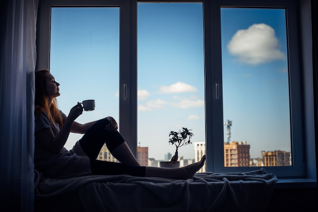 Silhouette of young slender girl sitting on the windowsill at home, side view, copy space. outside the window blue sky and tall city buildings. red-haired woman holding cup, looking at the metropolis.