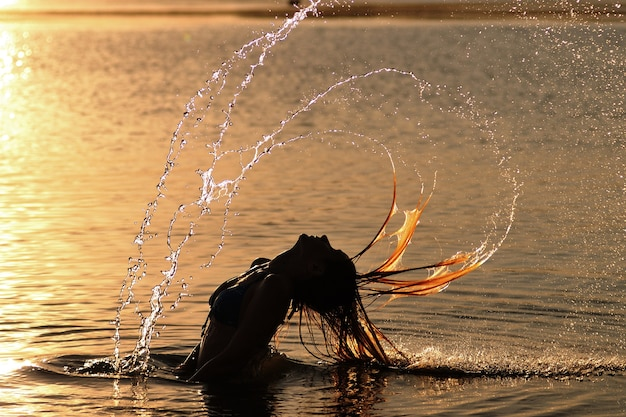 Silhouette of young woman in bikini standing in water and making water circles with hair at sunset on summer day. inner beauty and freedom concept