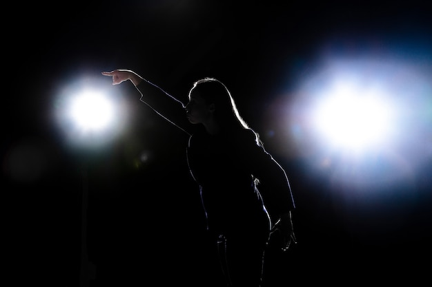 Silhouette of young woman gesturing isolated on black wall with flashlights. copyspace.