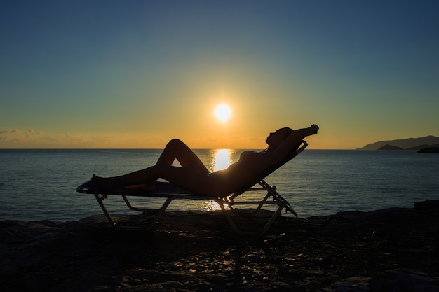 Silhouette of the young woman is lying on the deckchair at sunset