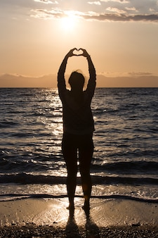 Silhouette of young woman making a hand shaped heart at sunrise on the beach.
