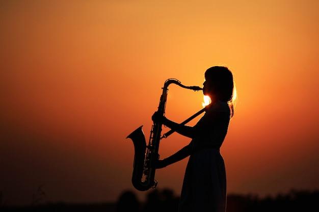 Силуэт молодой женщины, играющей на саксофоне во время заката, таиланд