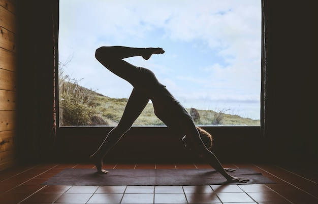 Silhouette of young woman practicing yoga indoor on background of big window with natural landscape