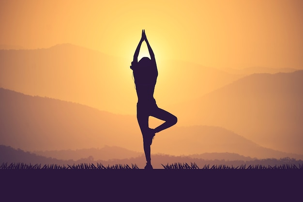 Silhouette young woman practicing yoga on the muontain at sunset.vintage color