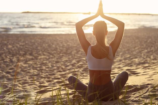 Силуэт молодой женщины упражнениями йоги на пляже на закате