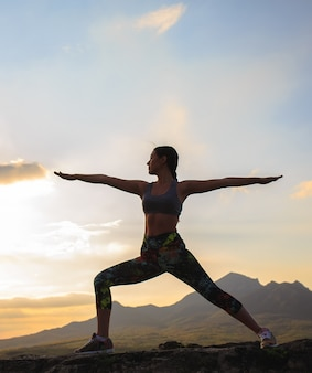 Silhouette of young woman practicing yoga or pilates at sunset or sunrise in beautiful mountain location.