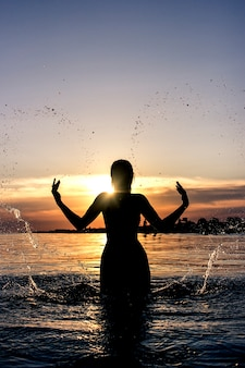 Silhouette of a young woman with splashes of water in the shape of a heart on a  of the sea
