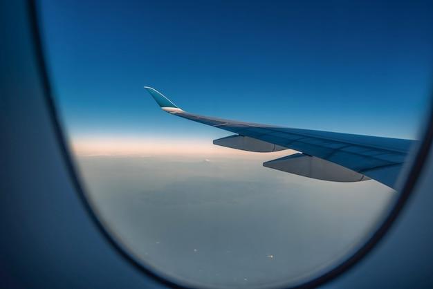 Silhouette крыло самолета на взгляде восхода солнца через окно.