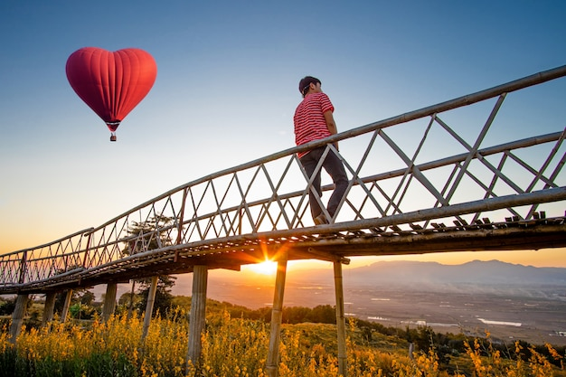 Silhouetted of asian man standing on bamboo bridge with red hot air balloon in the shape of a heart over the  sunset.